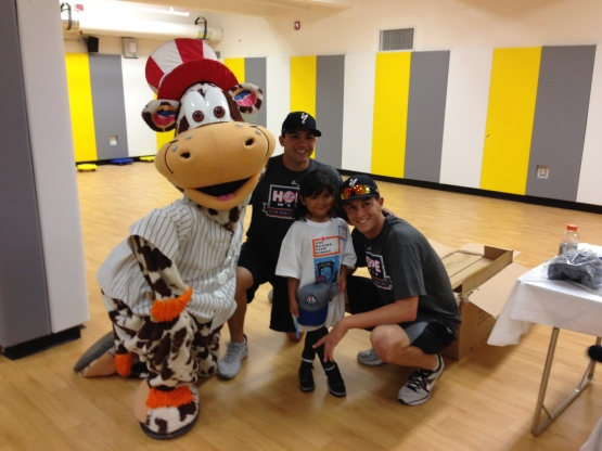 Scooter the Holy Cow, Eric Jagielo, and pitcher Andy Beresford posing with an excited student